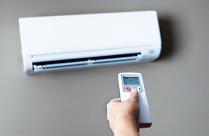 A ductless AC unit installed on a wall with remote control